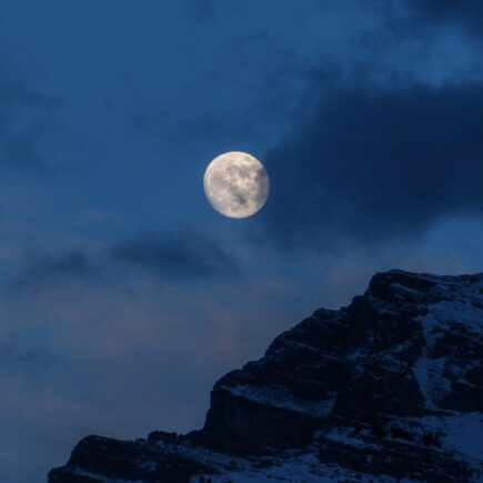 snowy mountain under full moon during nighttime