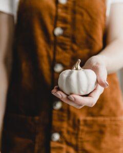 person holding white ceramic heart ornament